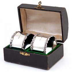 Pair of Boxed Edwardian Silver Napkin Rings with Plain Bodies and Floral and Scroll Borders